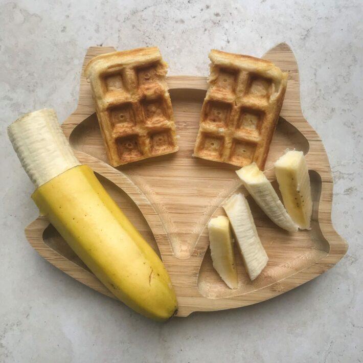 Sweet potato waffles on a bamboo bamboo plate served alongside banana