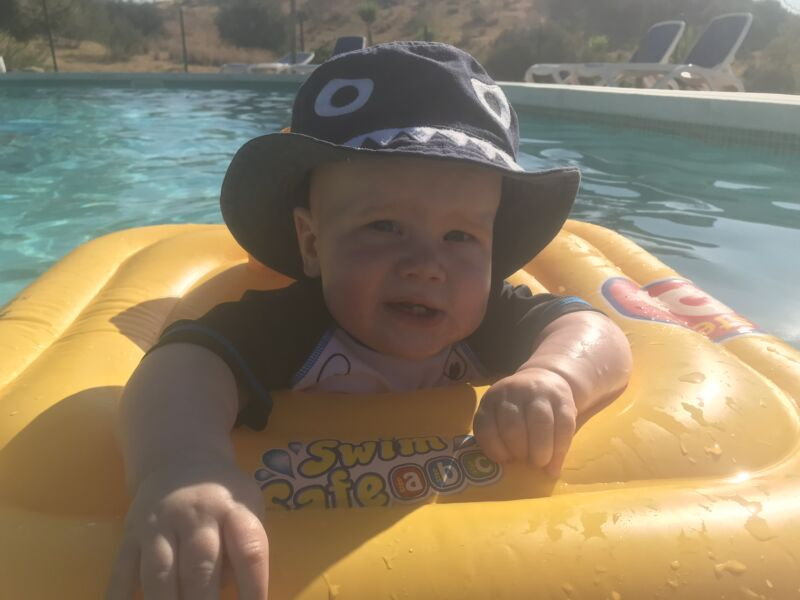 Felix in the pool in his yellow inflatable pool aide wearing a blue sun hat