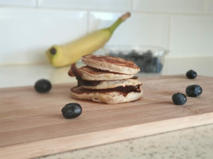banana pancakes surrounded by blueberries on a chopping board