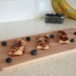 eggy bread for babies surrounded by blueberries on a chopping board