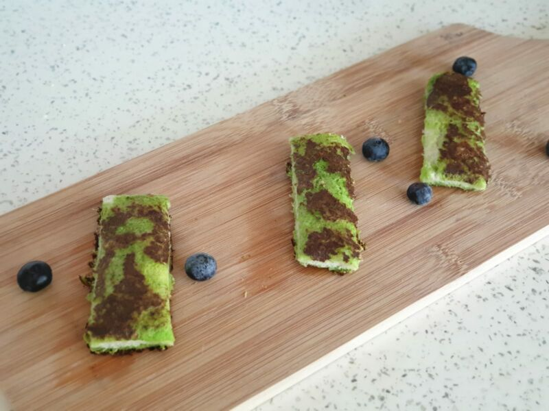 spinach eggy bread for babies on a chopping board surrounded by blueberries