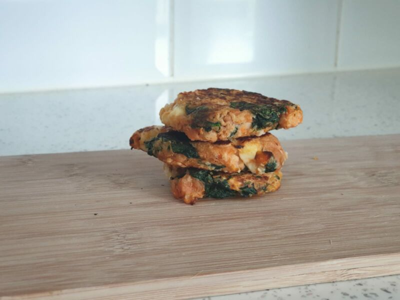 chicken, quinoa and spinach burgers on a chopping board in the kitchen