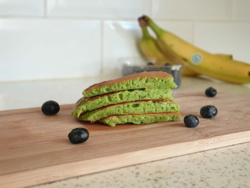 spinach and banana pancakes on a chopping board surrounded by blueberries
