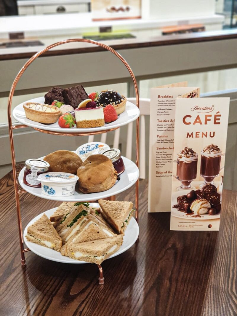 Cake and sandwiches stacked on afternoon tea tray next to a menu in Thornton's new store in Liverpool One