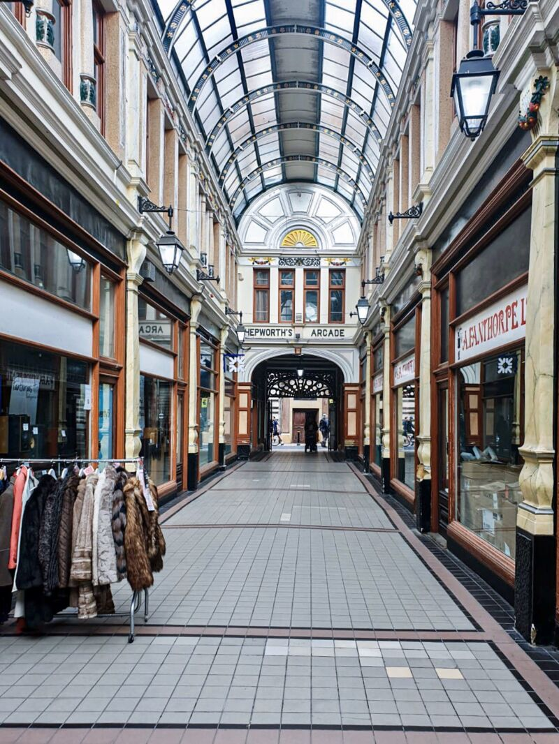 Hepworth Arcade with glass ceiling and rack of clothes outside one of the independent shops