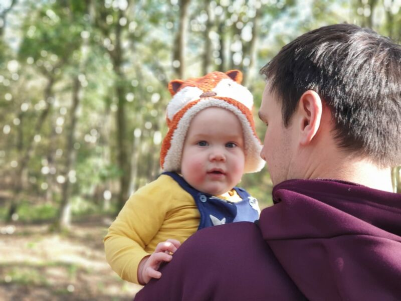 Felix wearing a Fox hat being carried by dad in formby pinewoods