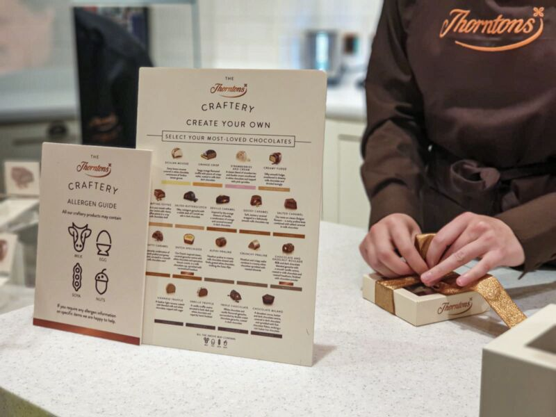 Thornton's employee wrapping our crafted chocolates next to a sign describing each chocolate