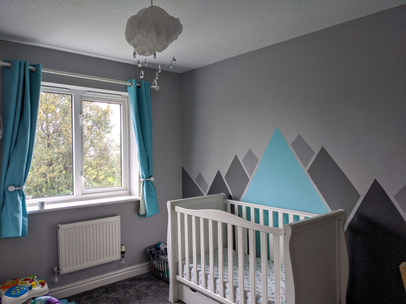 Felix's bedroom with grey and turquoise mountains on the wall, a big white cot and turquoise curtains