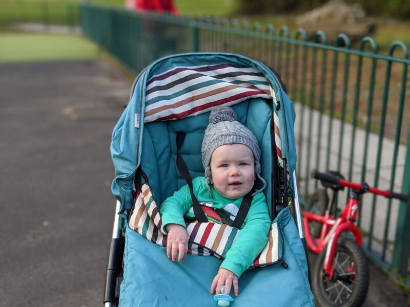 Felix in his green pram in the park wearing a grey hat and smoking