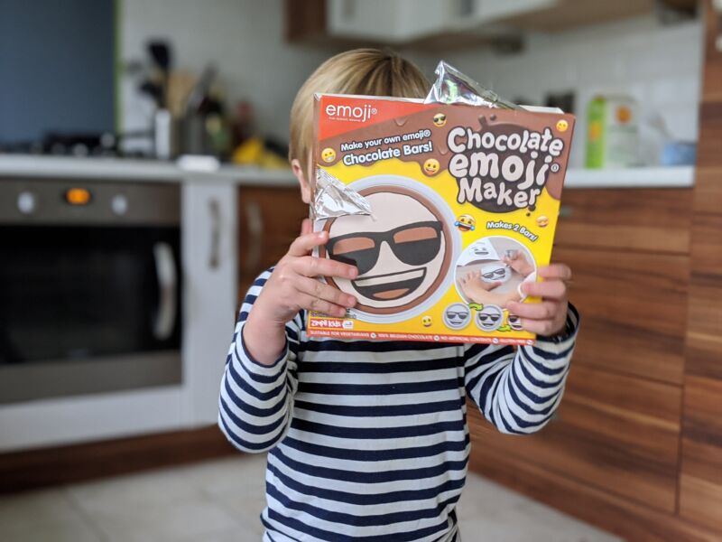 Dexter in the kitchen holding the box of chocolate emoji maker by zimpli kids