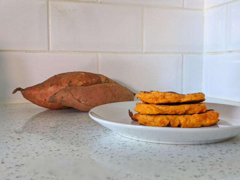 Sweet potato pancakes on a white plate with sweet potatoes in the background