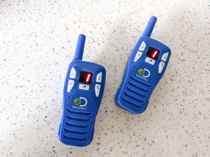 The Discovery walkie talkies on a white surface with the LED screen turned on
