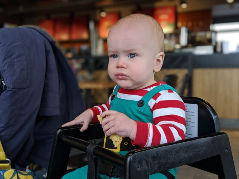 Felix wearing a Christmas outfit sat in a wooden highchair in Starbucks