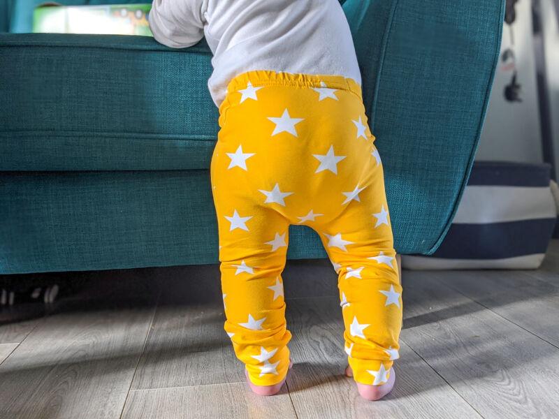 Felix wearing bright yellow leggings stood at the sofa