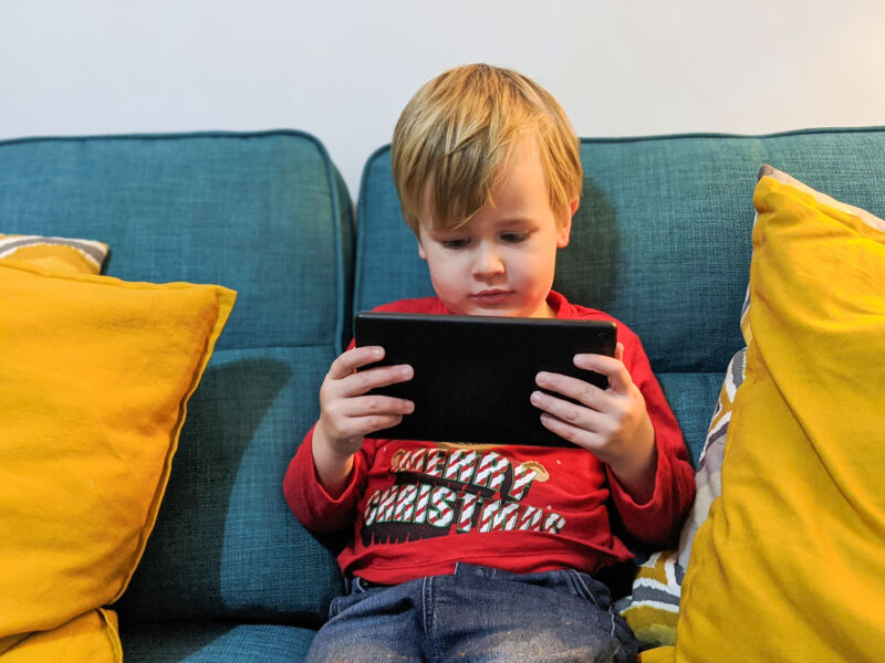 Dexter sat on the sofa with tablet in his hand watching Ricky Zoom