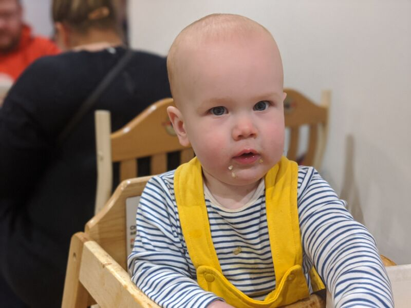 Felix wearing yellow dungarees sat in a highchair in Trafford Centre