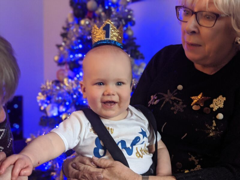 Felix wearing a birthday hat sat on his cousin's knee in front of a christmas tree at his birthday party
