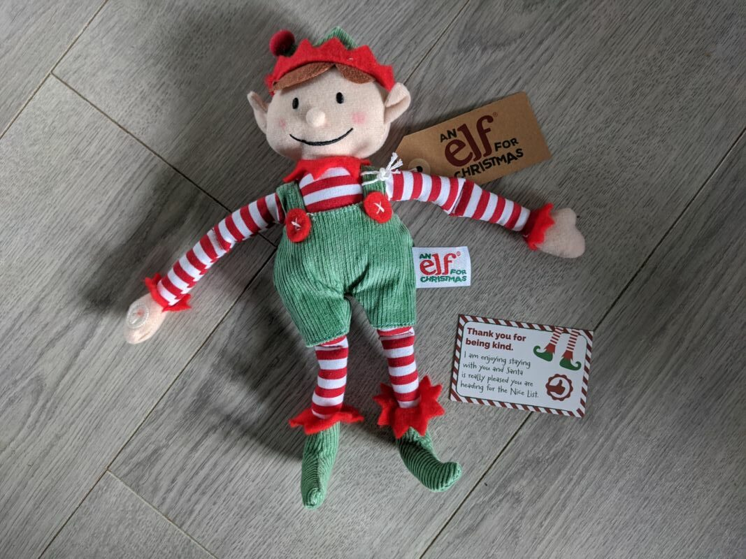 elf for christmas wearing green dungarees and a red hat