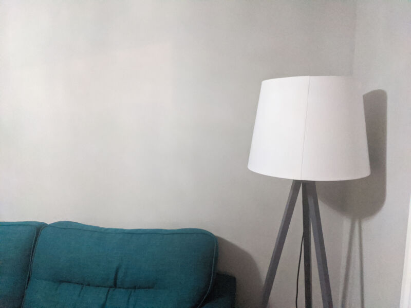 The grey walls of our lounge behind a teal sofa and grey and white lamp