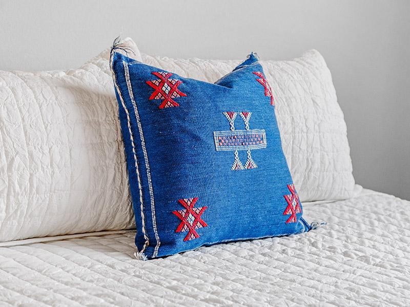 A blue cushion on a white sofa