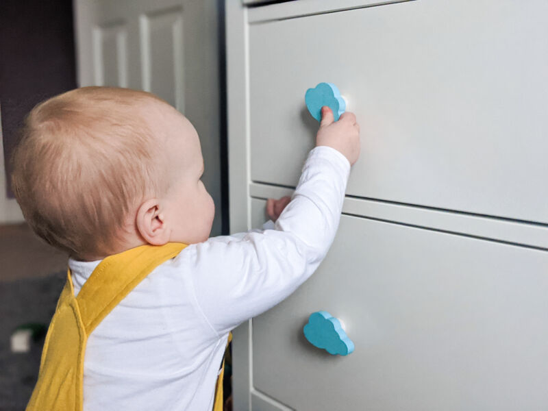 Felix in his bedroom, touching the turquoise painted drawer handles on his IKEA HEMNES drawers