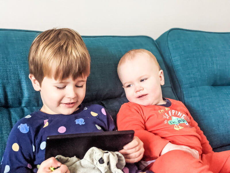 Felix and Dexter in their pyjamas watching the tablet sat on sofa