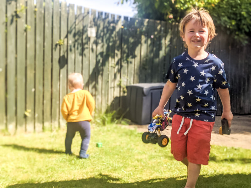 Decter in the garden holding his monster truck with Felix in the backgorund