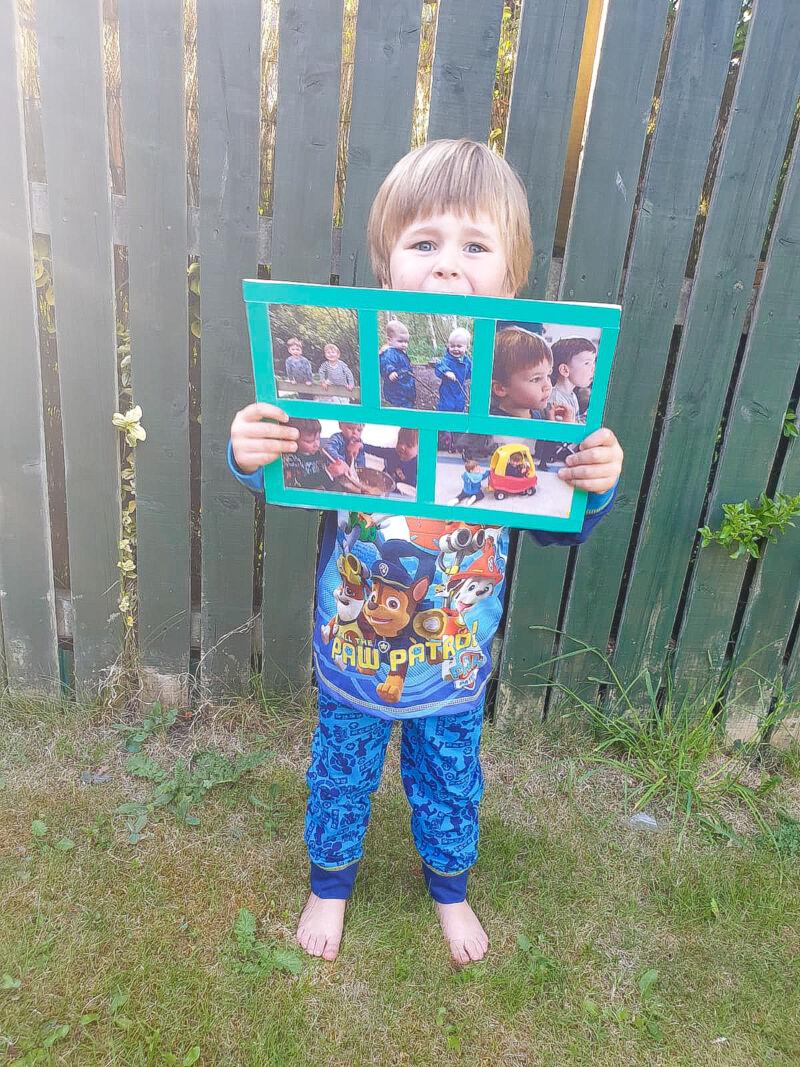 Dexter in Paw Patrol pyjamas holding a handmade birthday card from his best friend