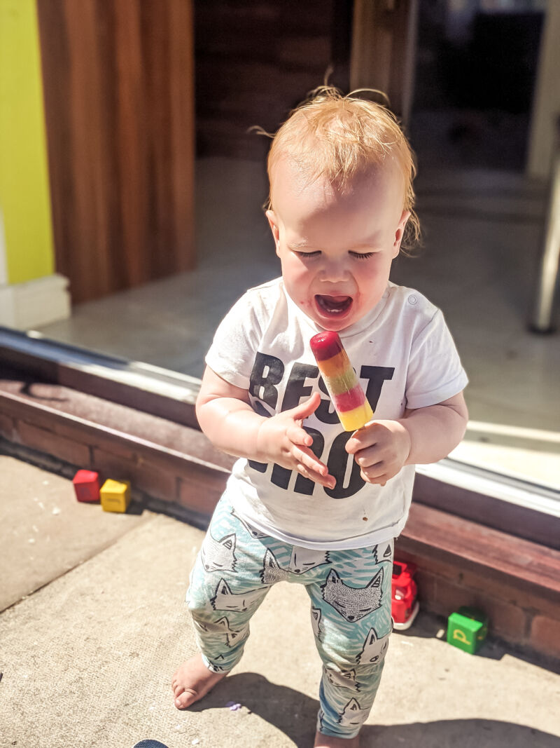 Felix eating an ice lolly in the garden wearing best bro t-shirt