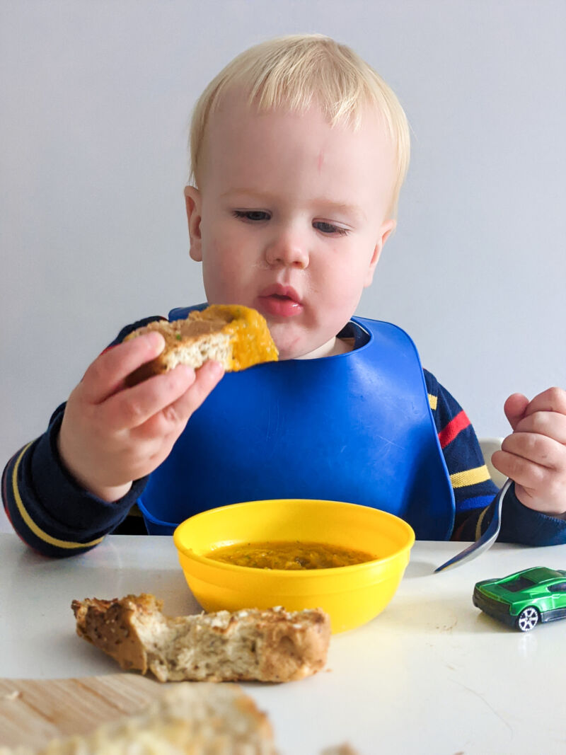 Felix dipping bread into carrot and coriander soup