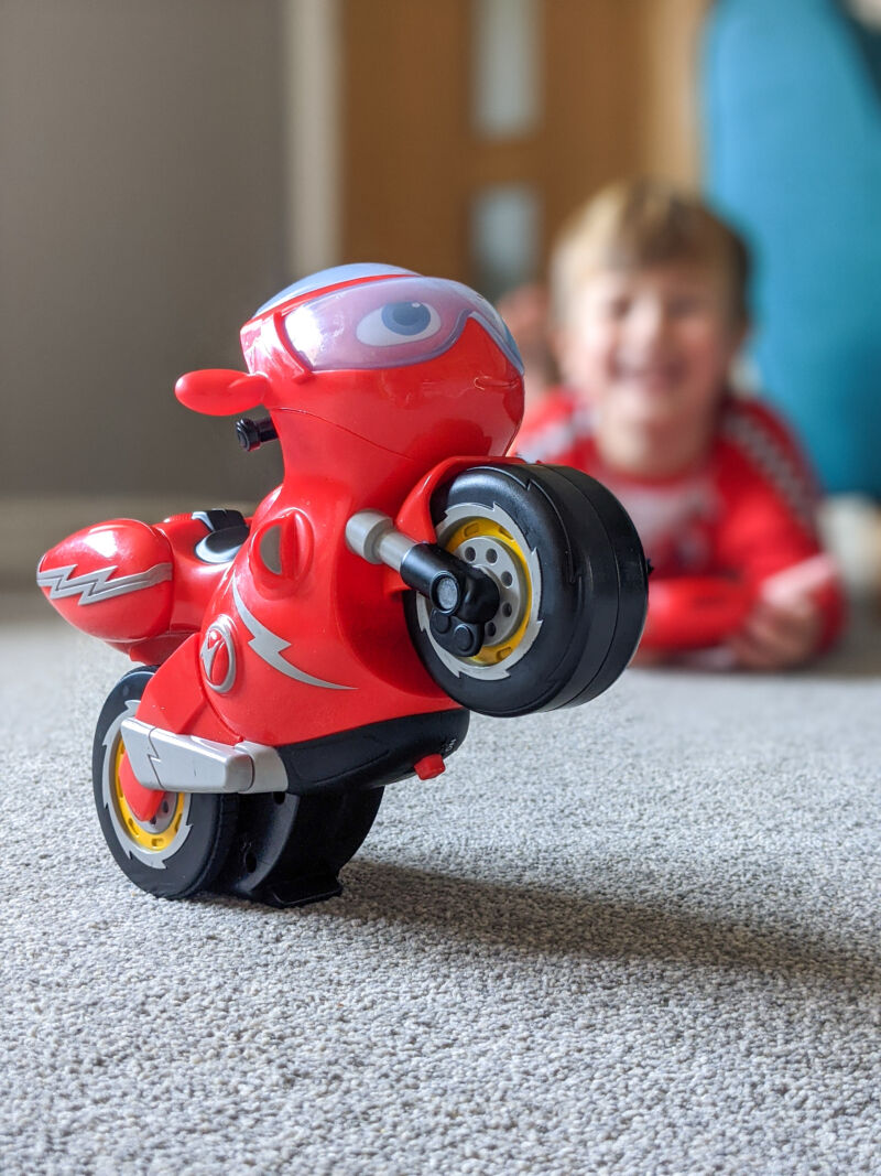 Ricky Zoom Turbo Trick TRicky standing up on one wheel with Dexter in the background controlling