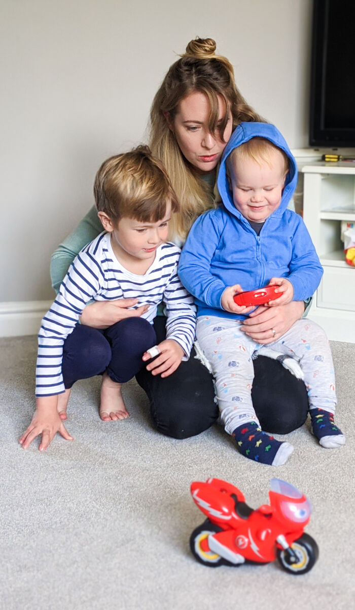 Nicola holding Dexter and Felix whilst Felix controls the Ricky Zoom Turbo Trick remote control toy