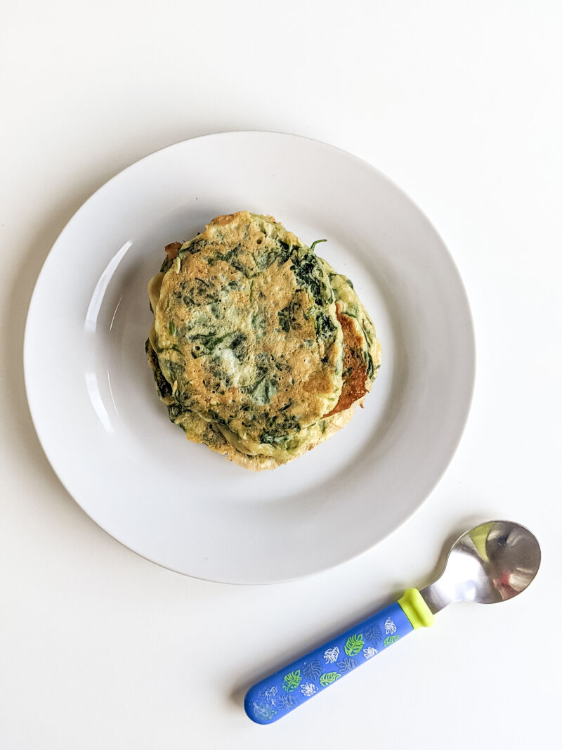 spinach fritters for baby on a plate next to spoon
