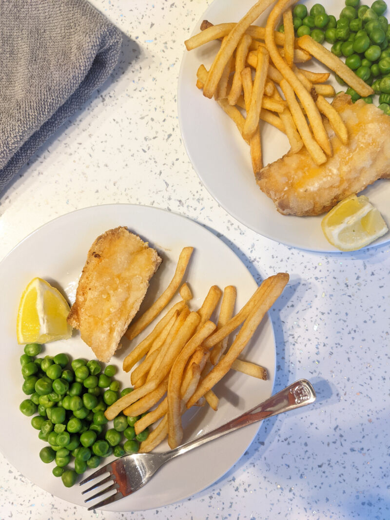 fish and chips for toddlers served up on a plate with a wedge of lemon and peas
