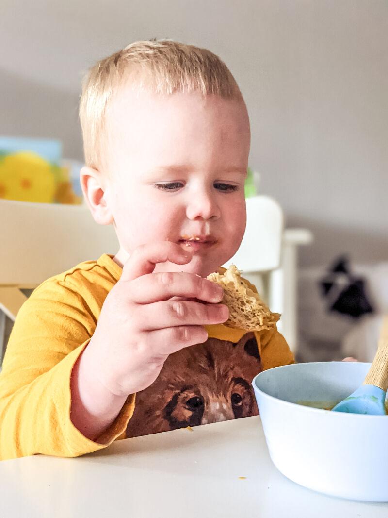 Felix dipping bread into the sweet potato soup