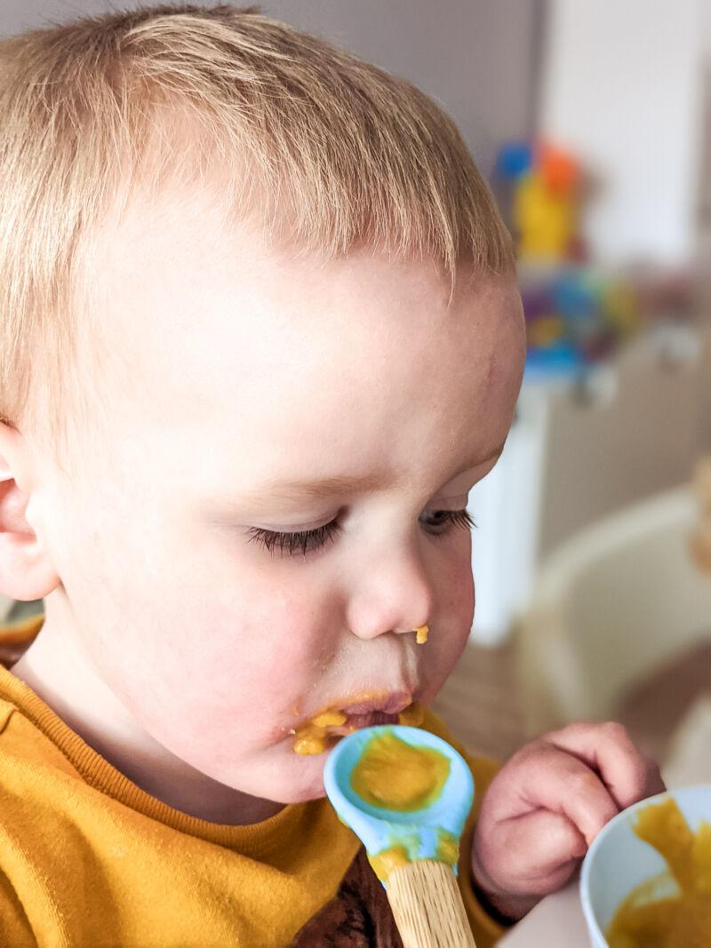 Felix using a spoon to eat sweet potato soup