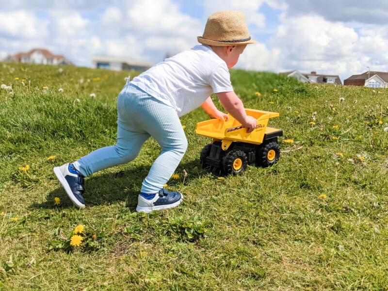 Felix pushing the Tonka Dump truck up a grassy hill