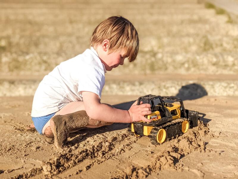 Dexter pushing the Tonka Steel Classics Bulldozer in the sand