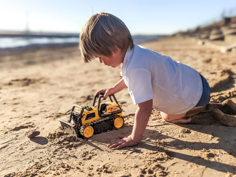 Dexter playing with the Tonka Steel Classics Bulldozer on the beach