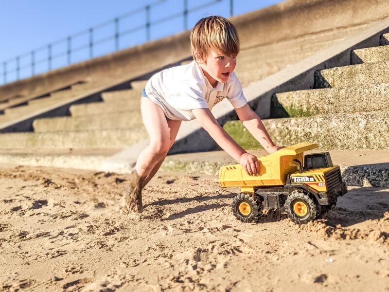 Dexter pushing the Tonka Dump Truck on the sand