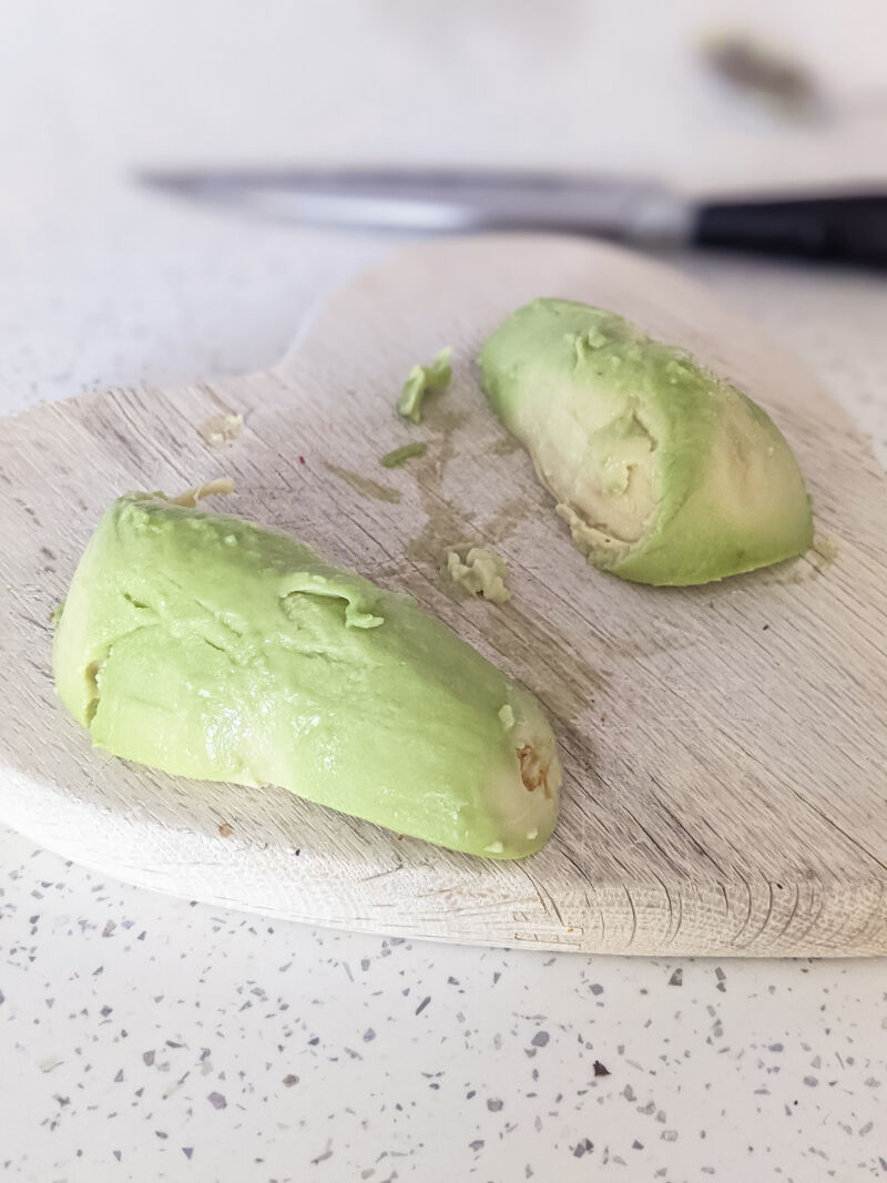 Two halves of an avocado, scooped out from the skin
