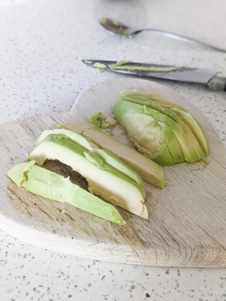 scooped avocado sliced on a chopping board