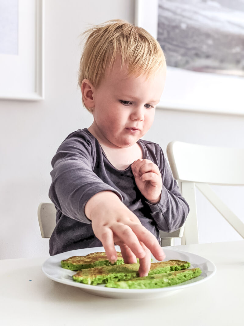 Felix eating banana and spinach pancakes at the table